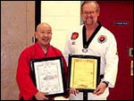Presentation of a Canadian and Korean 1st Dan black belt certifications to student Chris Pollach by Master Stephen Yeoh